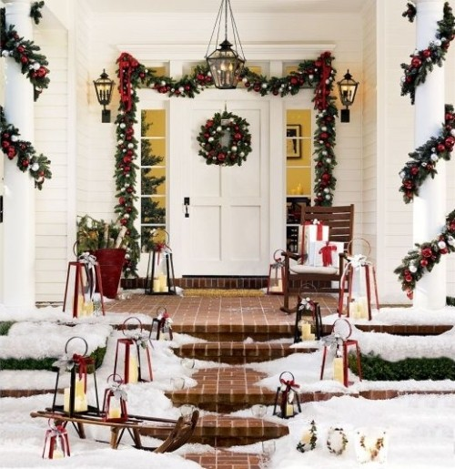 a bright Christmas porch with lots of lanterns, a sleigh, a bucket with birch branches, an evergreen garland with lots of ornaments over the door and on the pillars