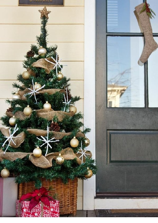 a Christmas tree with gold ornaments, pinecones, snowflakes in a basket is a lovely rustic decoration for your porch