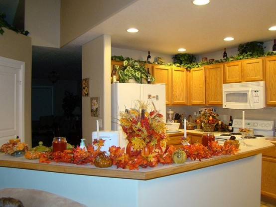 a bright faux fall leaf arrangement with pumpkins for decorating a fall kitchen - a durable and simple idea