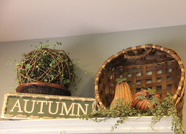 a vine ball with greenery, a basket with faux gourds and faux greenery plus a simple sign for a fall kitchen