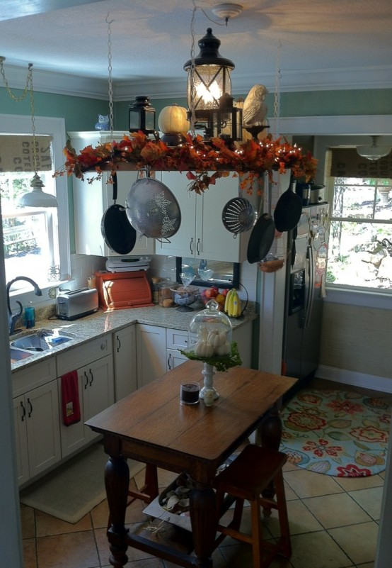 a suspended shelf with bright faux leaves, pumpkins and porcelain figurines for a fall kitchen