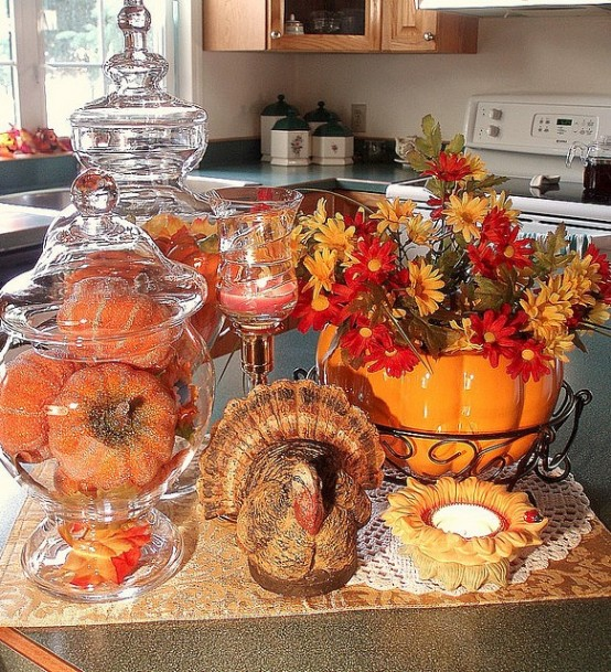 faux orange pumpkins in a glass jar, a bright pumpkin pot with fall blooms and a porcelain figurine