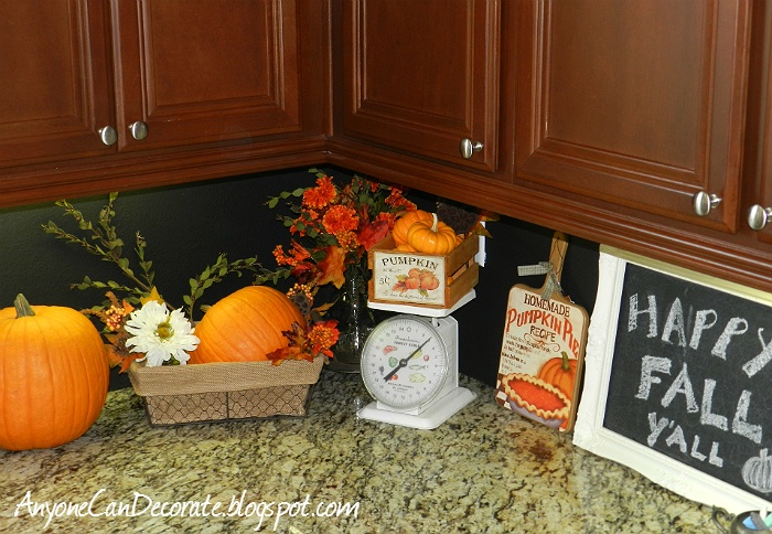 bright orange fall pumpkins and bright fall blooms, a crate with fake pumpkins for fall kitchen decor