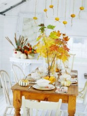 a tablescape spruced up with a lush fall leaf arrangement, pumpkins and some pumpkins hanging over the table