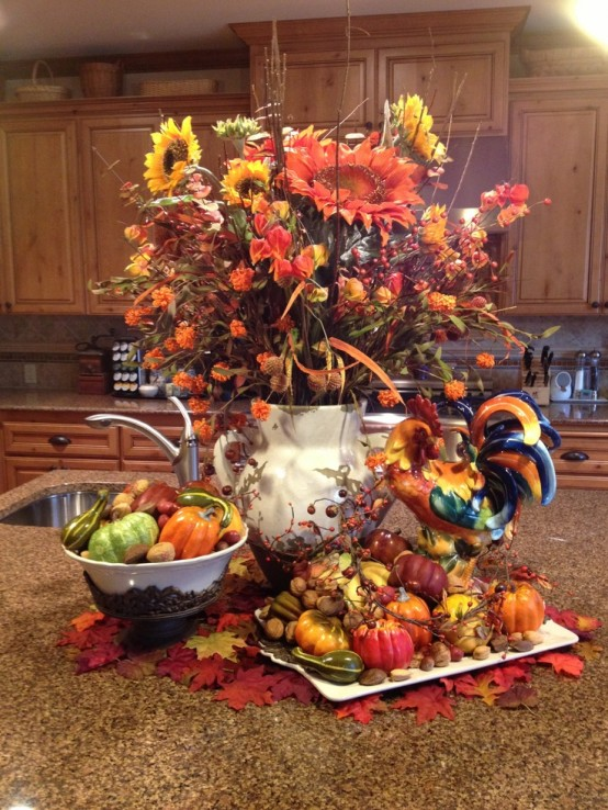 a white jug with bright fall branches, blooms and berries, faux pumpkins and gourds for decorating the table