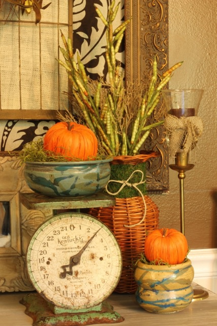 bright faux pumpkins, branches and wheat for giving a rustic and vintage fall touch to the kitchen