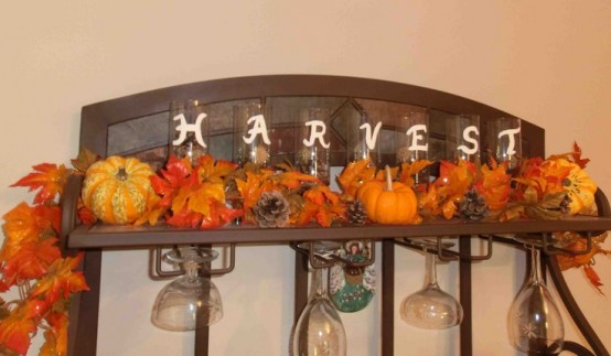 faux leaves, pumpkins and pinecones placed on a shelf is a very cool rustic-inspired idea