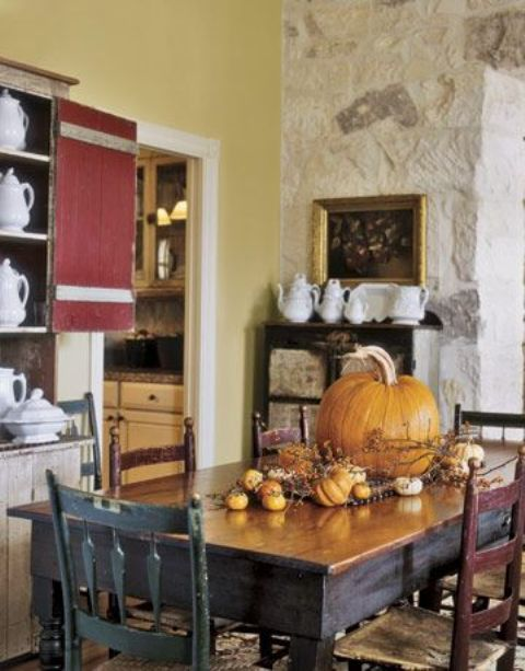 a cool and traditional fall centerpiece of a large pumpkin and some smaller pumpkins plus berries and branches