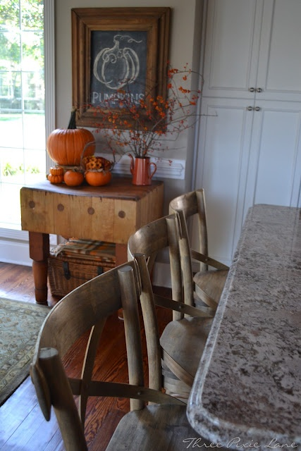 a small console with orange pumpkins, branches with berries in a jug, an orange basket with fall blooms