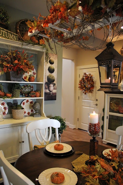faux fall leaves and bloom arrangements, berries, moss and nuts plus candles for decorating a fall kitchen