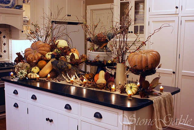 a kitchen island decorated with oversized faux pumpkins, gourds, antlers, branches, berries and figurines