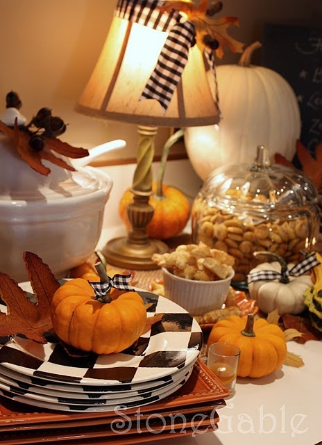 checked black and white plates, faux pumpkins with plaid ribbons and dried fall leaves for styling a tablescape for a party