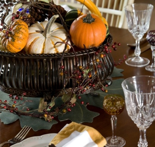 a fall centerpiece of a bowl filled with fake fruits and vegetables, with berries and twigs will last as long as you'll want