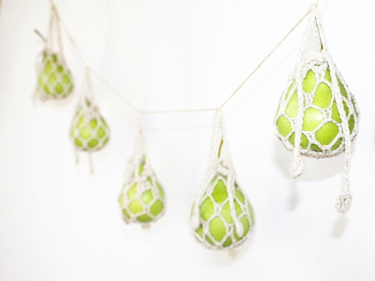 a creative garland of green apples wrpaped with macrame is a cool idea for the fall