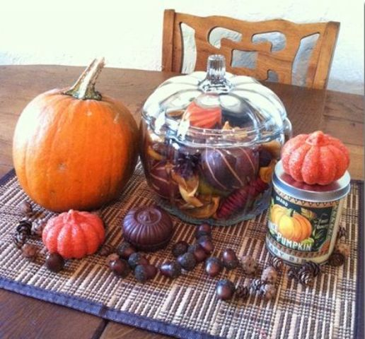 fall table decor with acorns, faux and natural pumpkins, a glass jar with pinecones, leaves and faux fruits and veggies