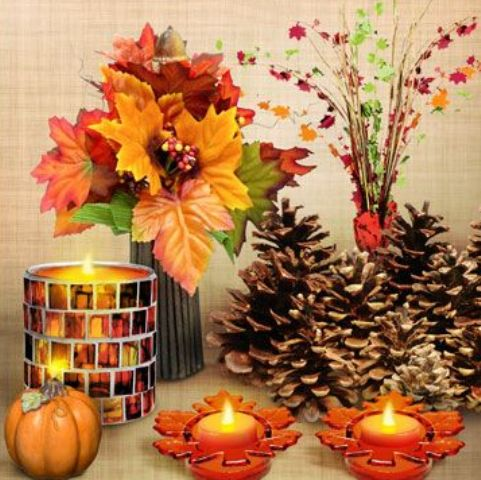 large pinecones, candles in fall candleholders, a faux pumpkin and an arrangement of fall leaves