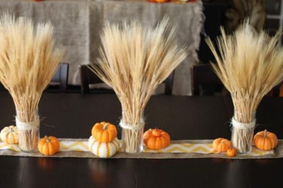 wheat arrangements, faux pumpkins and a burlap table runner for a stylish rustic tablescape