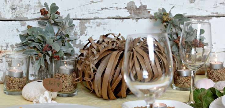 pale greenery, candles in glasses with seeds, a pumpkin made of paper ribbons for fall party decor