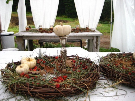 a vine wreath with grass, berries and white pumpkins is a nice fall party centerpiece idea