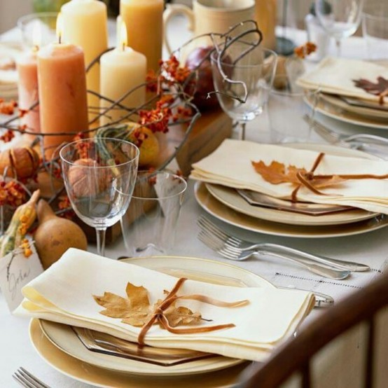 a chic and natural fall tablescape with fresh fruits, dried blooms, twigs, candles and fall leaves to mark each place setting