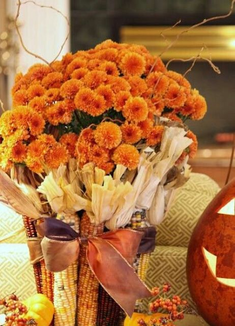 a fall party centerpiece with bright orange blooms covered with corn with husks is a very cool harvest-inspired decoration