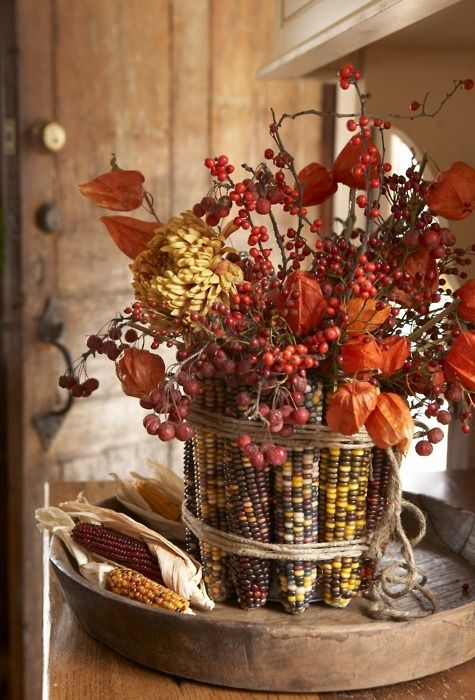 a fall centerpiece of berries and dried blooms covered with corn cobs and husks for a more natural look