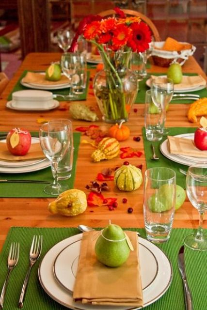 a colorful fall aprty table setting with bright green placemats, faux veggies and fresh apples and pears plus bright florals
