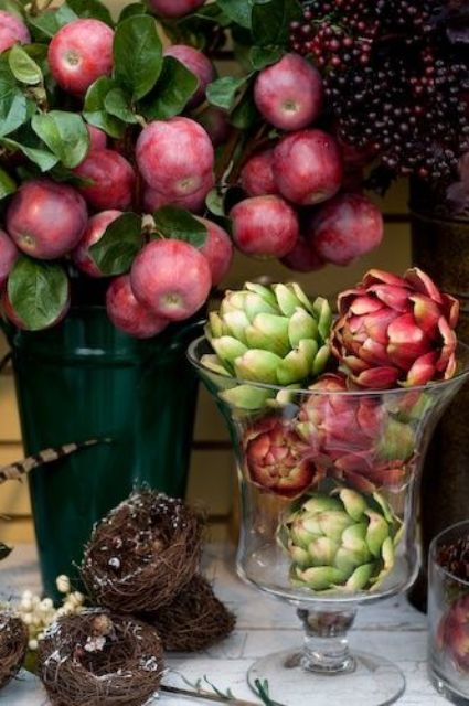 a alrge and tall glass vase with artichokes is a great idea for a fall centerpiece or just as a decoration