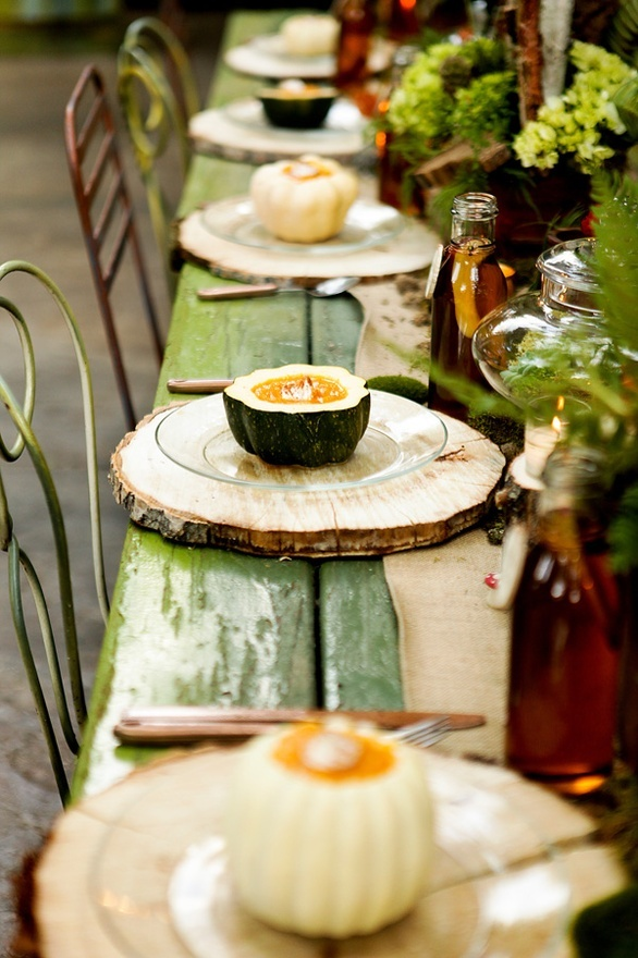 a natural fall tablescape with an uncovered table, natural pumpkins, greenery arrangements and wood slices instead of placemats