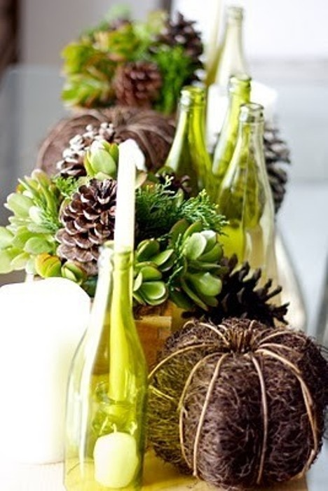 a fall centerpiece of pinecones, vine and usual white pumpkins, candles, greenery and green bottles