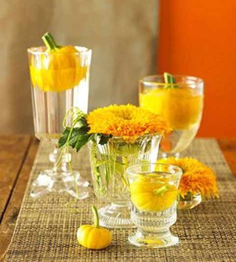 a bright fall party centerpiece of glasses with floating yellow blooms and pumpkins is a whimsy and easy idea