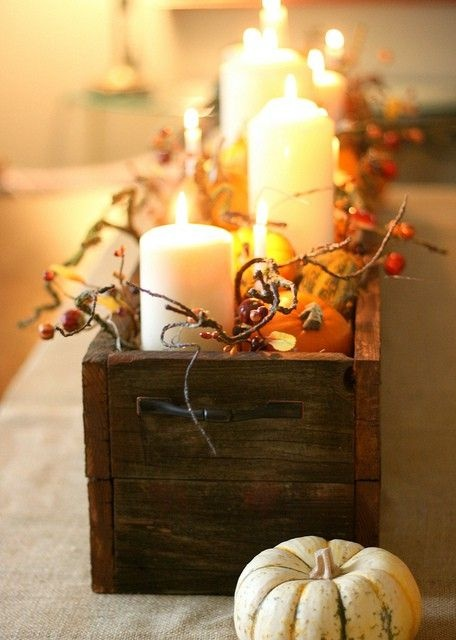 a wooden box with berries, pumpkins, candles and some pumpkins around for a rustic feel