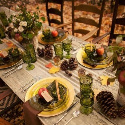 a stylish fall party tablescape with green glasses and plates, gold chargers and cutlery, pincones, fall leaves and fall floral arrangements