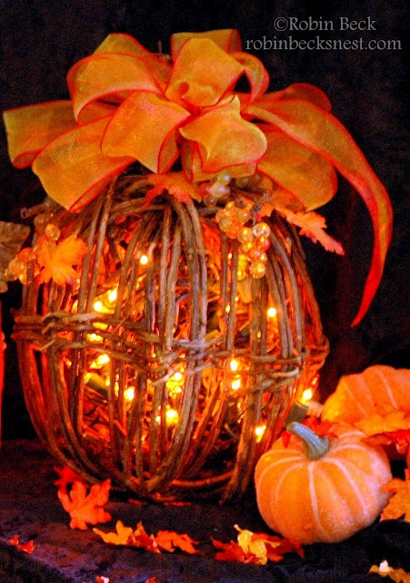 a vine pumpkin with lights, beads and orange ribbons plus faux orange leaves all around