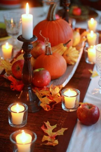 a wooden tray with natural pumpkins, gourds and apples plus leaves and candles around for a cute and easy fall centerpiece