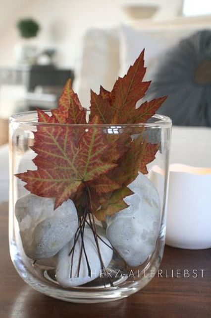 a glass with pebbles and fall leaves is a simple and cool decoration for fall parties with a natural feel