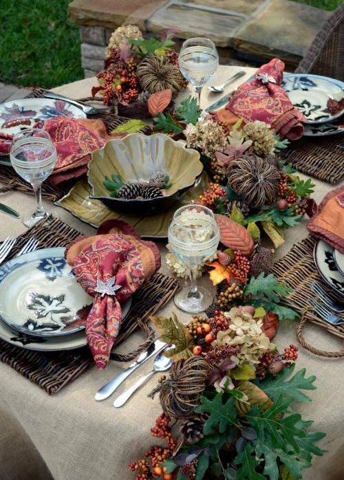 a traditional fall tablescape with vine, faux berries, fruits and leaves, woven placemats and a metal bowl in the center