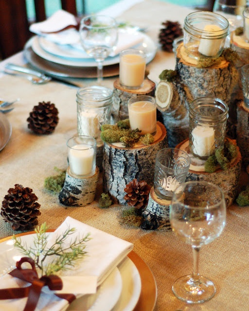 a rustic fall tablescape with a tree stump, candles and pinecones centerpiece and gold chargers and greenery for each place setting
