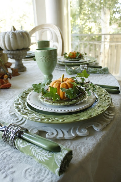 a pastel fall tablescape with green plates, napkins and cutlery, printed tablecloths and faux pumpkins and greenery