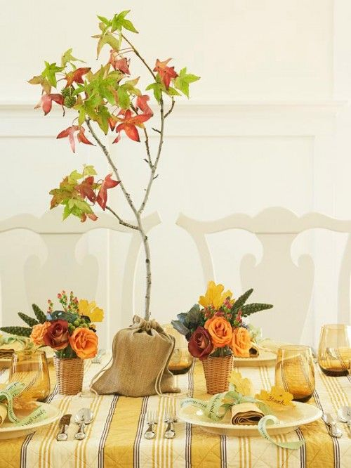 a bright fall tablescape with a plaid tablecloth, bright floral centerpiece and a fall tree in burlap plus mustard glasses