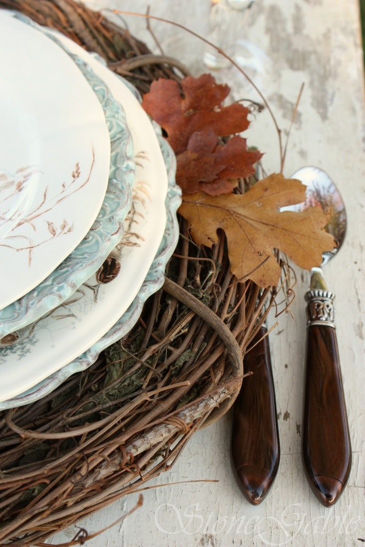 style place settings with woven placemats, printed plates and natural fall leaves