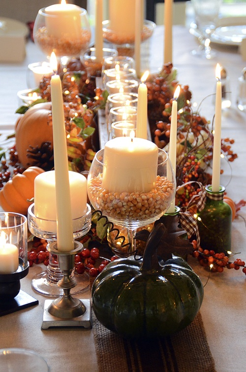a classic fall table setting with candles, faux pumpkins, pinecones, berries and other fall stuff