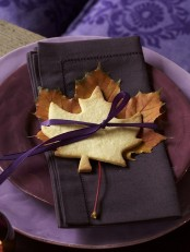 a place setting with layered fall plates, a dark napkin and fall leaves plus a fall leaf cookie on top