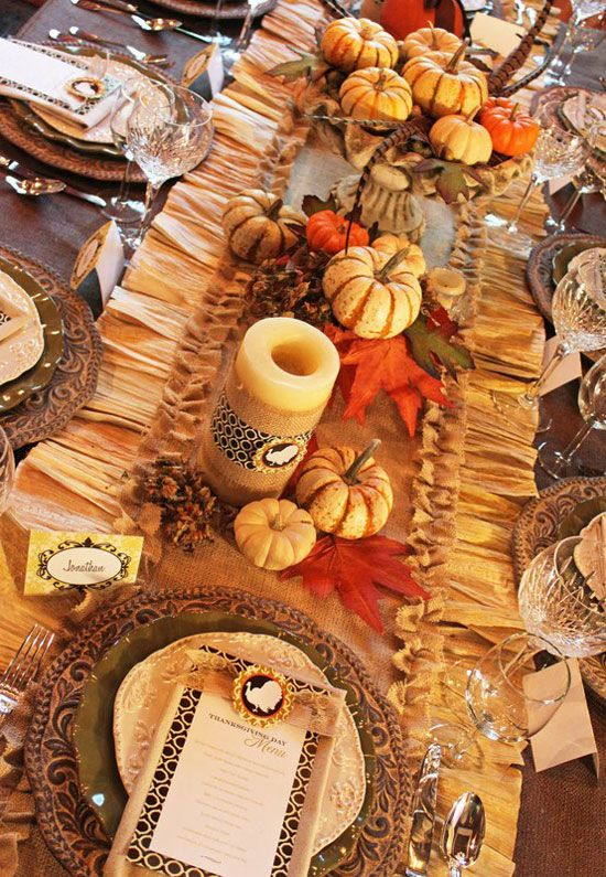 a colorful vintage table setting with a ruffle table runner, faux pumpkins and candles, woven placemats and fall leaves