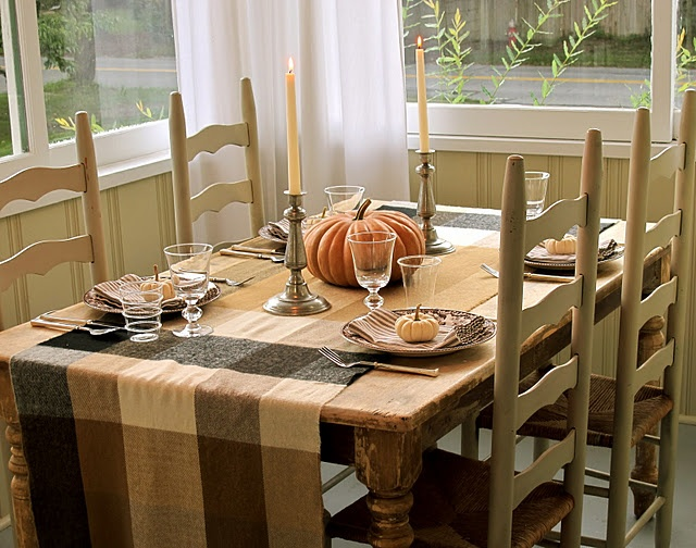 a neutral fall table setting with a plaid tablecloth, natural pumpkins and candles plus printed porcelain