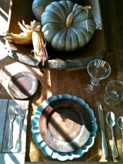 a moody rustic fall tablescape with an uncovered wooden table, shabby chc plates and a doughbowl with pumpkins and corn cobs
