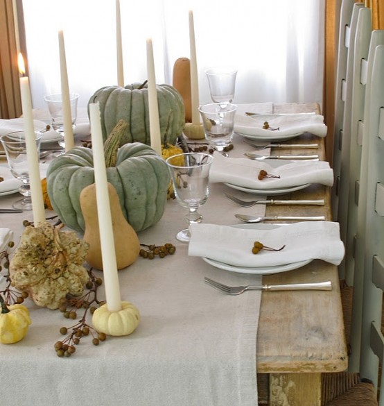 a neutral and natural fall tablescape with faux pumpkins and gourds, tall candles, berries and a neutral fabric table runner
