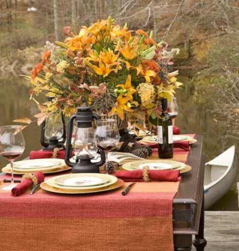 a colorful fall tablescape with a bright tablecloth, red napkins, pinecones, a lush arrangement of bold blooms and fall leaves