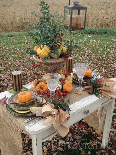 a vintage-inspired fall table setting with a burlap runner, printed plates, candles, faux pumpkins, berries, a vintage urn with greenery, pumpkins and berries