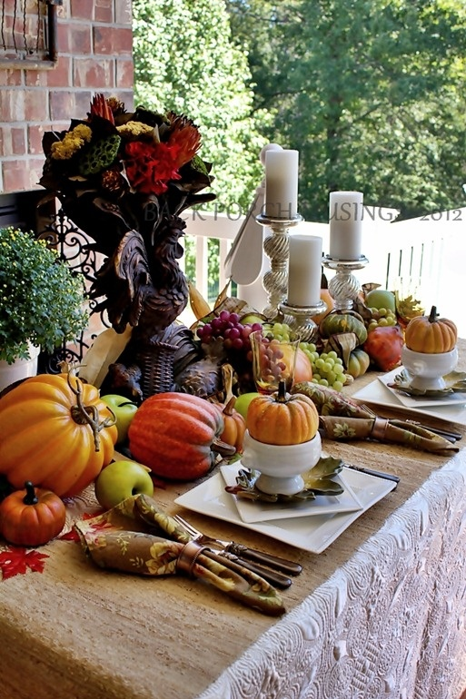 a vintage-inspired fall tablescape with printed napkins, faux pumpkins, berries and veggies, candles in neutral candle hohlders and a centerpiece with bold blooms